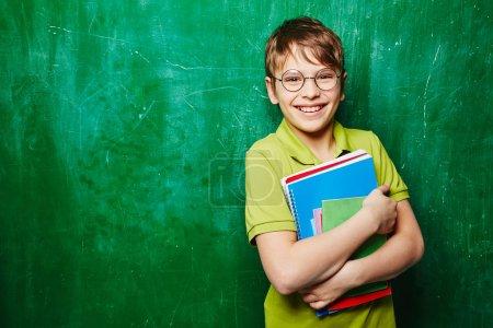Photo pour Beau garçon avec des livres regardant la caméra par tableau vert - image libre de droit