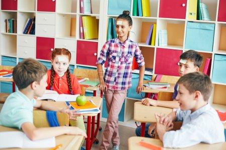 """Foto de Amigos de la escuela jugando a """"quién soy"""" durante la rotura en aula - Imagen libre de derechos"""