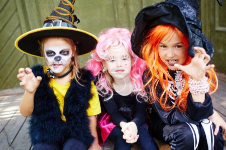 Photo for Little girls in Halloween costumes looking at camera with frightening expression - Royalty Free Image
