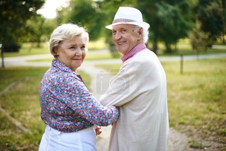 Photo for Happy senior couple looking at camera during walk in park - Royalty Free Image