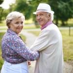 Happy senior couple looking at camera during walk ...
