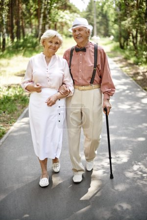Photo for Affectionate couple of seniors in smart casual going down park road - Royalty Free Image