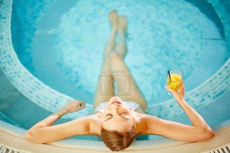 Woman in bikini relaxing in swimming pool