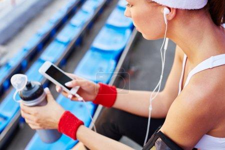 woman in activewear using smartphone