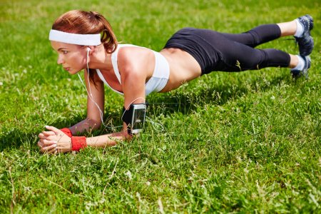 Sporty woman practicing pushups