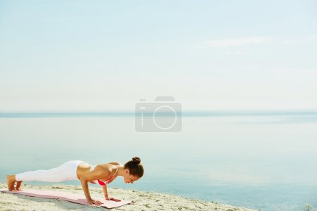 woman doing pushups by the seaside
