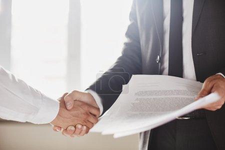 Photo pour Homme d'affaires avec des documents félicitant son associé. Nouvelle entente - image libre de droit