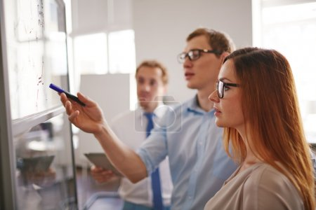 businesswoman looking at information on board with colleague explanations