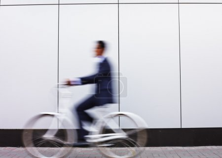 Businessman in suit riding bicycle