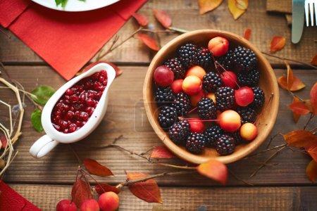 Photo pour Table avec bol de mûres et de cerises avec canneberge preserve, vue de dessus - image libre de droit