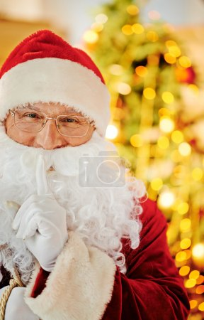 Photo for Santa Claus looking at camera with his forefinger by mouth - Royalty Free Image