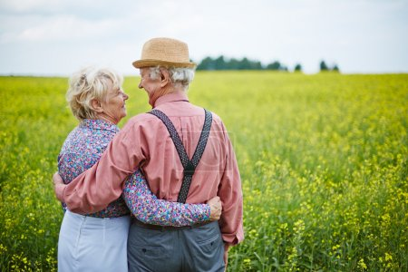 senior couple enjoying summer day in meadow
