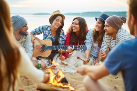 girls and guys singing by guitar