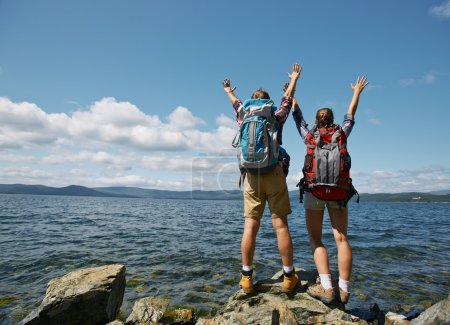 Photo for Couple of travelers with raised arms enjoying summer vacation by the sea - Royalty Free Image