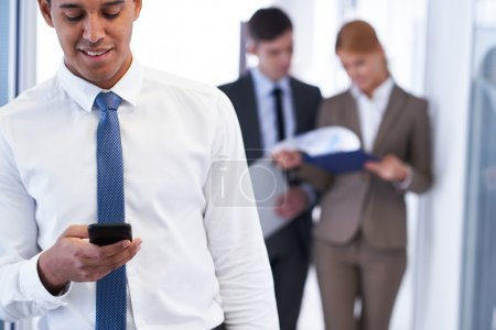 Businessman with cellphone reading sms