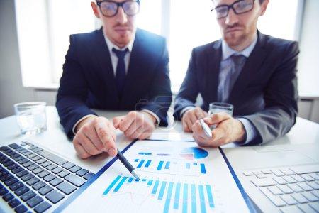 Photo pour Gros plan de deux hommes d'affaires pointant vers le tableau dans le document dans le bureau - image libre de droit