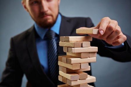 Photo pour Homme d'affaires mettant petit bloc en bois sur le dessus de la tour, gros plan - image libre de droit