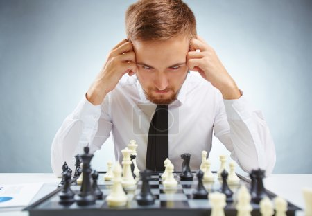 businessman looking at chessboard