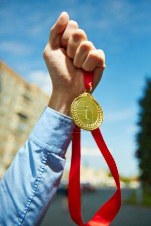 businessman showing gold medal