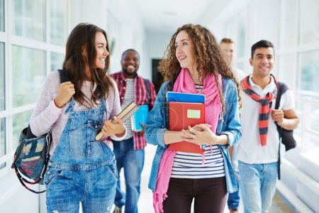 Photo for Happy teenage girls walking along college corridor and talking  with groupmates on background - Royalty Free Image