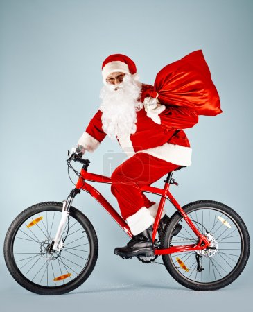 Photo for Santa Claus holding sack with gifts while riding bicycle - Royalty Free Image