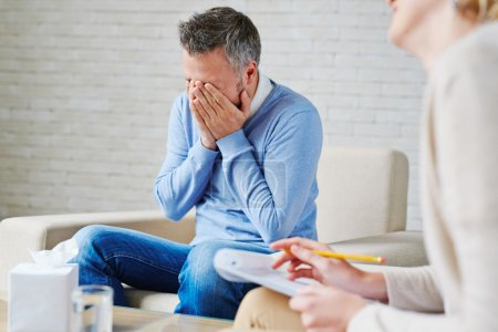 Photo for Stressed man with his hands on face sitting by psychologist - Royalty Free Image