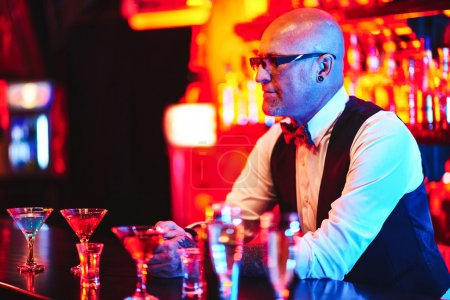 Photo for Bald barman standing by counter with drinks in night club - Royalty Free Image