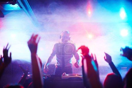 Photo pour DJ masculin debout près des platines tournantes devant la foule dansante à la discothèque - image libre de droit