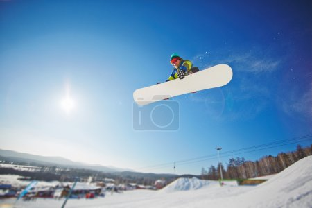 Sportsman snowboarding in winter