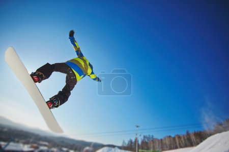 Photo for Sportsman snowboarding in winter over blue sky - Royalty Free Image