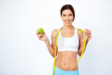 woman with green apple and measuring tape