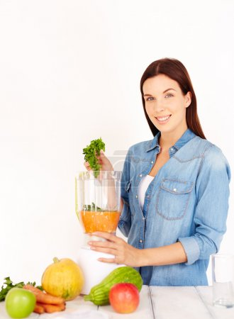 woman making smoothie from fresh vegetables