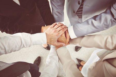 Photo pour Mains des partenaires d'affaires faire tas, vue de dessus - image libre de droit