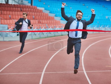 Photo for Young running businessman reaching finish at stadium with his rival on background - Royalty Free Image