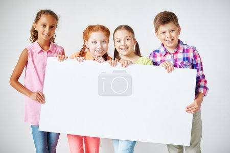 Photo pour Heureux écoliers tenant du papier vierge et regardant la caméra - image libre de droit