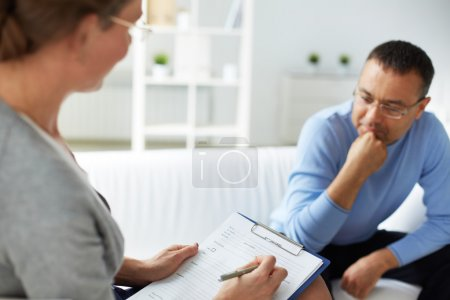 psychologist with document listening to man