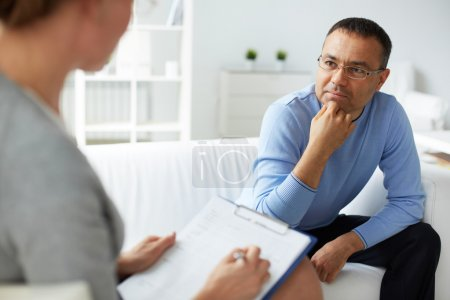 man in eyeglasses listening to psychologist