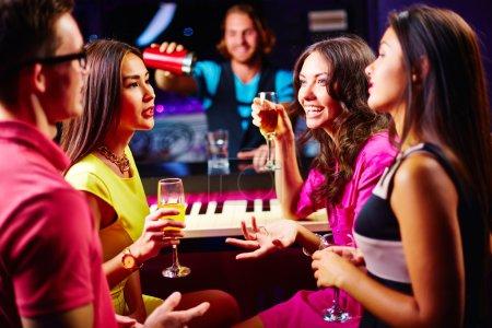 Photo pour Jeunes amis, parler au partie tout en buvant du champagne - image libre de droit