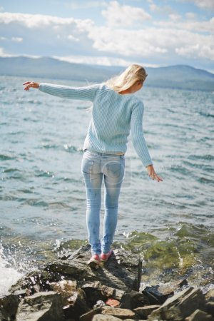 Photo for Rear view of blond girl in jeans and pullover standing on stone by the seaside - Royalty Free Image