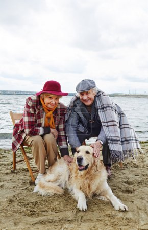 senior couple with dog resting on beach