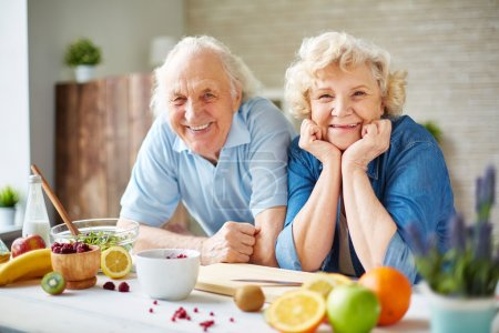 Photo for Happy senior man and woman looking at camera in the kitchen - Royalty Free Image