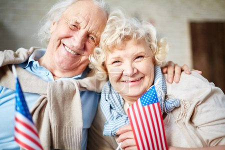 Photo for Smiling seniors with flags of USA looking at camera - Royalty Free Image