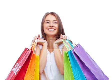 Photo pour Souriant jeune femme tenant des sacs à provisions colorés dans les deux mains isolées sur fond blanc - image libre de droit