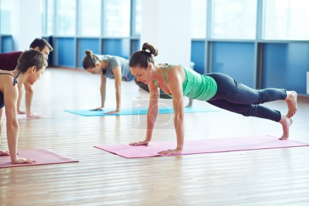 people doing yoga exercise in gym