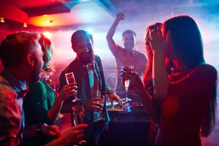 Photo pour Jeunes gens qui dansent à party avec Dj en boite de nuit - image libre de droit