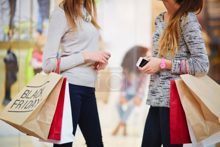 friends communicating in shopping mall