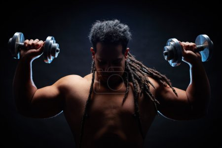 Photo for Rear view of strong man with dreadlocks working out with barbells in gym on black background - Royalty Free Image