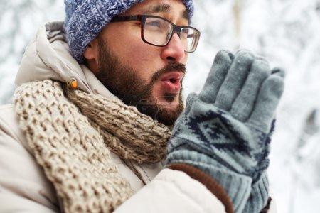 Photo pour Asiatique gars en hiver usure et gants essayant de se réchauffer les mains à l'extérieur - image libre de droit