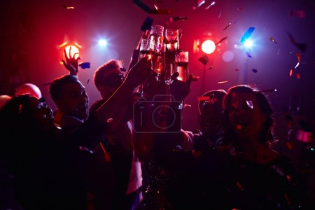Photo for Young friendly people toasting in night club - Royalty Free Image