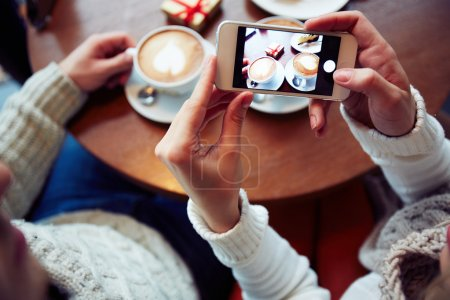 Girl holding smartphone with photo